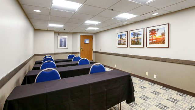 Conference room with 4 rows of tables and 8 chairs
